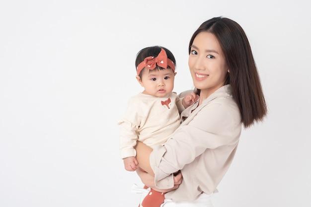 Azjata matka i urocza dziewczynka są szczęśliwi na biel ścianie