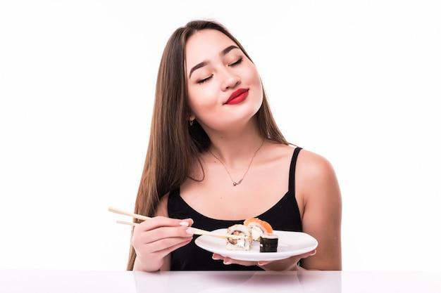 Azjata modelu trzymać pałeczki z sushi rolki na białym tle