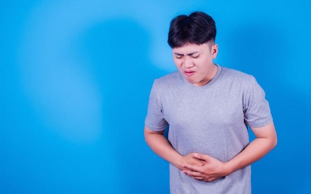 Azjata nosi t-shirt cierpiący na ból brzucha, bo ma biegunkę na niebieskim tle