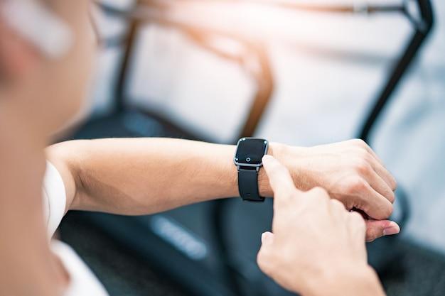 Azjata obsługujący smartwatch na siłowni
