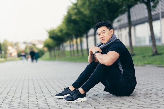 Azjata po treningu fitness i joggingu siedzący na ziemi zmęczony odpoczynkiem
