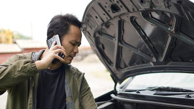 Azjata podczas rozmowy otworzył maskę samochodu