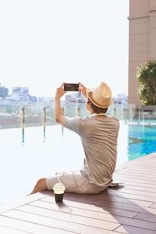 Azjata robi zdjęcie tła basenu za pomocą smartfona
