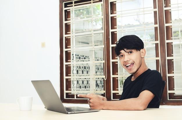 Azjata siedział, wskazując na laptopa