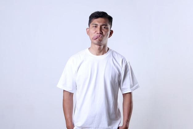 Azjata ubrany w białą koszulkę z głupkowatym wyrazem twarzy, który szarpie usta