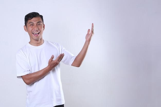 Azjata w białej koszuli z wesołym wyrazem twarzy i prezentujący coś