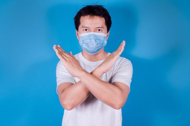 Azjata w medycznej masce na twarz, aby chronić covid-19 (koronawirus), przestań wychodzić na zewnątrz, na niebieskim tle
