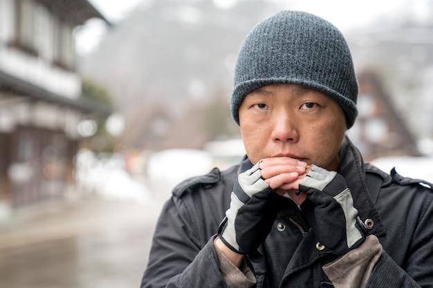Azjata w śnieżnym kapeluszu wpatruje się w kamerę i myśli coś, dolina shirakawako w tle sezonu śnieżnego.