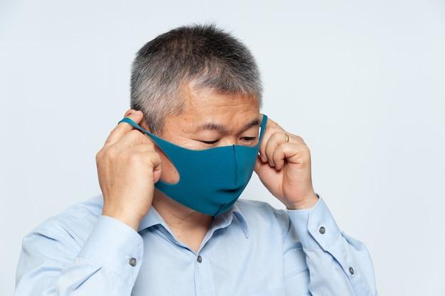 Azjata w średnim wieku zakładający poliuretanową maskę wielokrotnego użytku w celu ochrony przed covid-19. pojedynczo na białym tle.