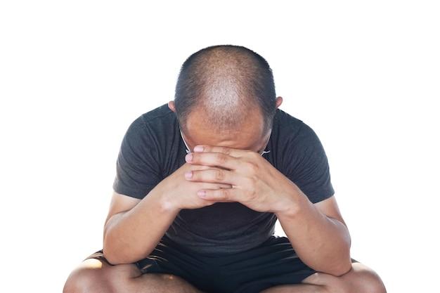 Azjata w szarej szacie siada ze spuszczoną głową, przygnębiony, zestresowany i łysina.