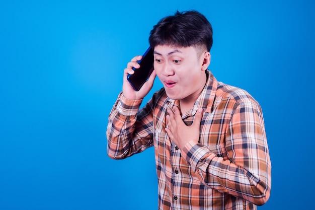Azjata wygląda na zaskoczonego dobrą wiadomością, jaką otrzymał ze swojego smartfona. mężczyźni pokazują zszokowane ruchy z wyłupiastymi oczami na smartfonie na niebieskim tle