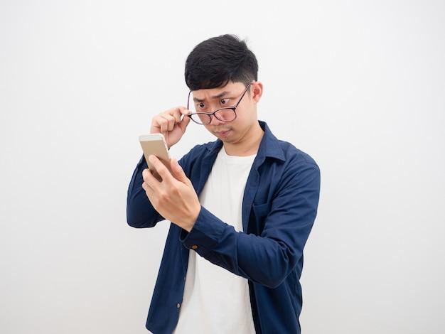 Azjata zdejmuje okulary, aby spojrzeć na telefon komórkowy w dłoni, czując zwątpienie i zszokowaną twarz na odrobinie szczęścia