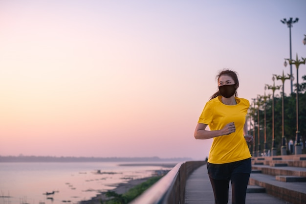 Azjatka biega i ćwiczy w masce ochronnej covid-19 rano na świeżym powietrzu nad brzegiem rzeki.