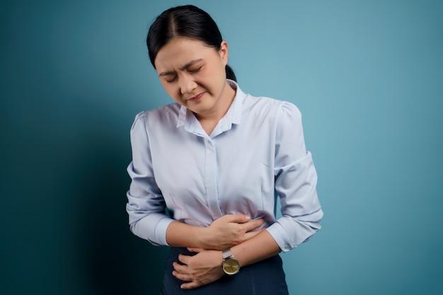 Azjatka była chora z powodu bólu brzucha, trzymając się za ręce uciskające jej brzuch