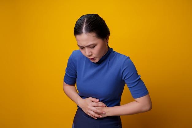 Azjatka była chora z powodu bólu brzucha, trzymając się za ręce uciskające jej brzuch.
