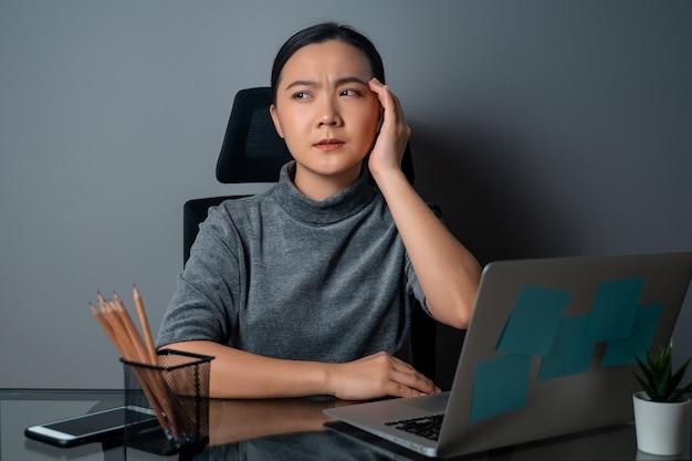 Azjatka chorowała na ból głowy, dotykała jej głowy, pracowała na laptopie w biurze