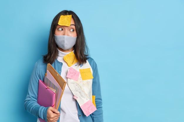 Azjatka, która utknęła w notatkach z przypomnieniem, nosi maskę ochronną, aby chronić się przed koronawirusem, trzyma foldery i wykonuje papierkową robotę.