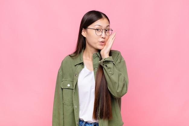 Azjatka młoda kobieta czuje się zszokowana i zdumiona, trzymając twarz w rękę z niedowierzaniem z szeroko otwartymi ustami