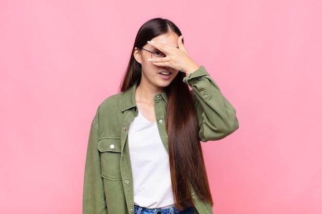 Azjatka młoda kobieta wyglądająca na zszokowaną, przestraszoną lub przerażoną, zakrywającą twarz ręką i zerkającą między palcami