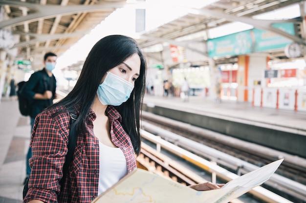 Azjatka nosząca chirurgiczną maskę na twarz przeciwko nowemu koronawirusowi lub chorobie koronawirusowej covid i czytająca mapę podróży na publicznym dworcu kolejowym zrelaksuj się i znajdź miejsce w pociągu powietrznym