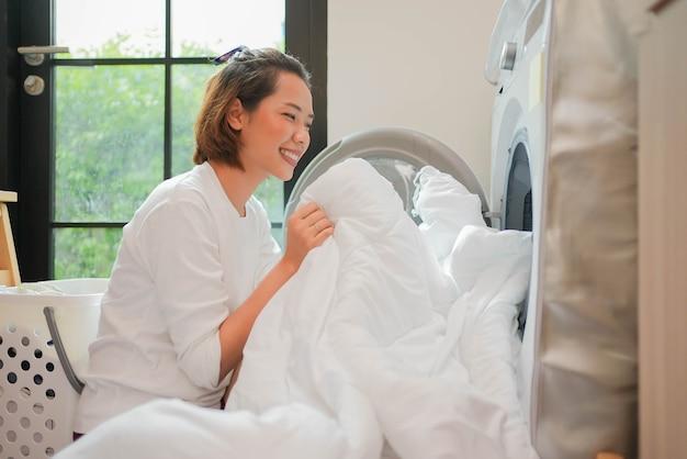 Azjatka pchająca koc do pralki, aby rozpocząć czyszczenie ubrań w pomieszczeniu gospodarczym