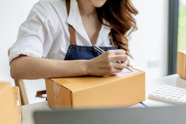 Azjatka pisząca informacje o wysyłce klienta na paczce, jest właścicielką sklepu internetowego, wysyła produkty do klientów za pośrednictwem prywatnej firmy kurierskiej. koncepcja sprzedaży online.