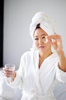 Azjatka przyjmująca lekarstwa po porannym przebudzeniu, kobieta w szlafroku i ręczniku ma leki przeciwbólowe, cierpi na poranne mdłości lub bóle głowy
