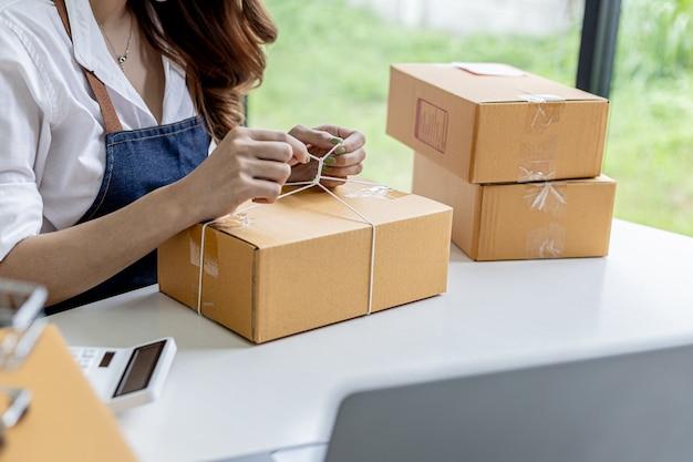 Azjatka przywiązująca paczkę do pudełka klienta, właścicielka sklepu internetowego, pakuje i wysyła za pośrednictwem prywatnej firmy transportowej. koncepcje sprzedaży i zakupów online.