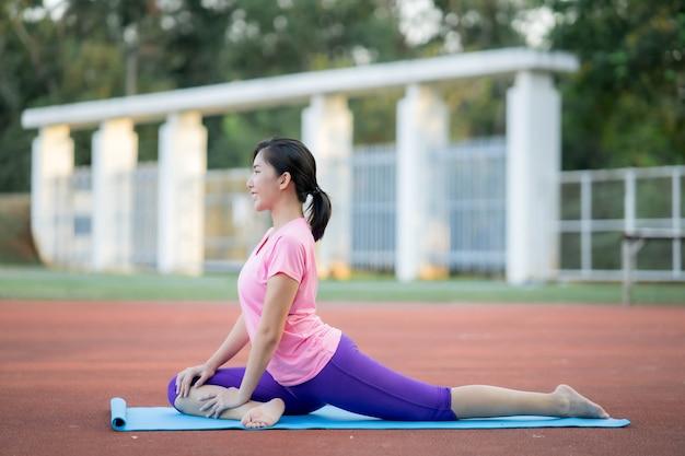 Azjatka rozciąga rozgrzane mięśnie swojego ciała przed wyjściem na bieg do parku