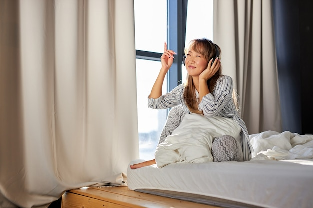 Azjatka słucha muzyki w słuchawkach siedząc na łóżku w piżamie, odpoczywa w domu