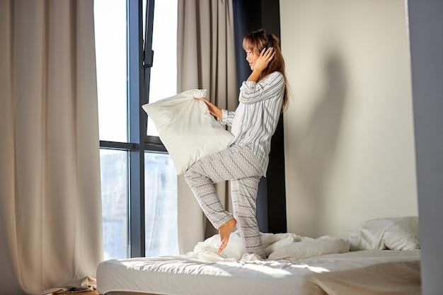 Azjatka słucha muzyki w słuchawkach stojąc na łóżku w piżamie, odpoczywa w domu