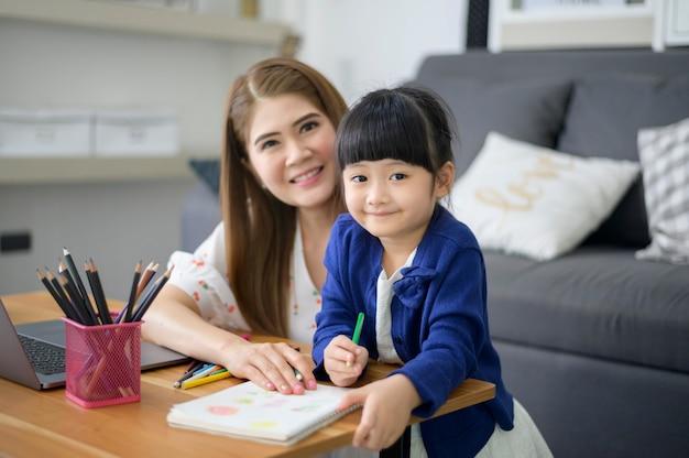 Azjatka szczęśliwa mama i córka używają laptopa do nauki online w domu. koncepcja e-learningu w czasie kwarantanny.