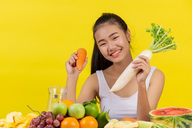 Azjatka trzymając marchewkę prawą ręką trzymaj rzodkiew lewą ręką, a na stole jest wiele owoców.
