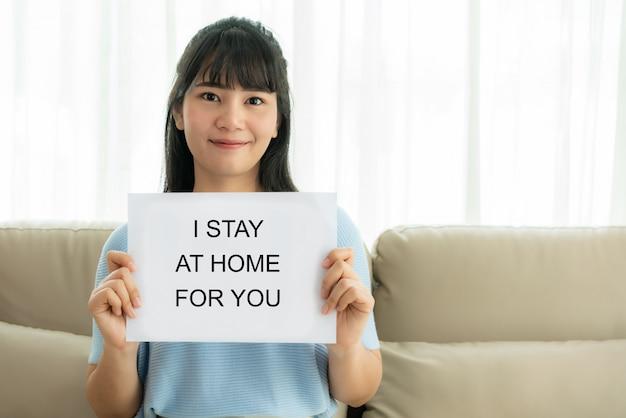 Azjatka trzymająca kartkę papieru z tekstem zostaję w domu, aby kibicować personelowi medycznemu w celu ochrony przed wirusem i dbania o jego zdrowie przed covid-19. pozostań w domu koncepcja.
