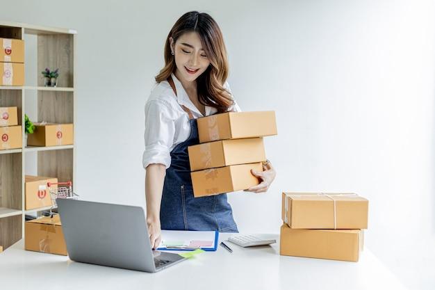 Azjatka trzymająca paczki i sprawdzająca zamówienia z laptopa, posiada sklep internetowy, pakuje i wysyła za pośrednictwem prywatnej firmy transportowej. koncepcje sprzedaży i zakupów online.