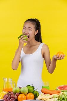 Azjatka trzymająca pomarańcze po obu stronach, a na stole jest wiele owoców.
