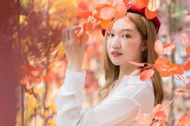 Azjatka ubrana w białą koszulę i czerwoną czapkę stoi w czerwono-pomarańczowym liściu jak las jesienią.