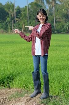 Azjatka ubrana w czerwoną koszulę w paski pozuje wskazując palcem na bok na polu na zewnątrz.