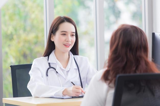 Azjatka, ubrana w fartuch medyczny i stetoskop, rozmawia z pacjentką, aby skonsultować się i zasugerować