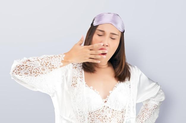 Azjatka ubrana w koronkową białą koszulę nocną i satynową szatę ziewająca, pokazująca senny gest zakrywający usta ręką.