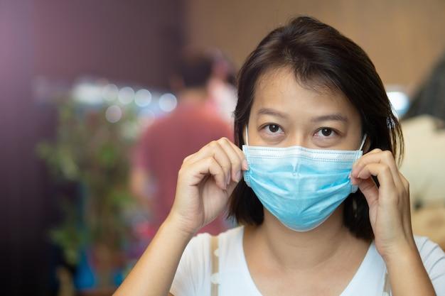 Azjatka ubrana w maskę ochronną na twarzy podczas pobytu w kawiarni podczas pandemii wirusa covid-19.