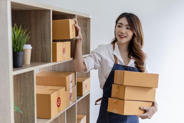 Azjatka układa na półce zapakowaną paczkę, aby przygotować ją do dostawy, jest właścicielką sklepu internetowego, pakuje ją i wysyła prywatną firmą transportową. koncepcje sprzedaży i zakupów online.