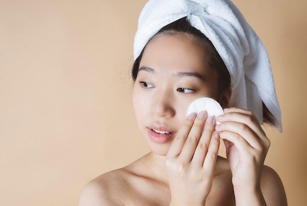 Azjatka usuwa makijaż, z ręcznikiem w głowie