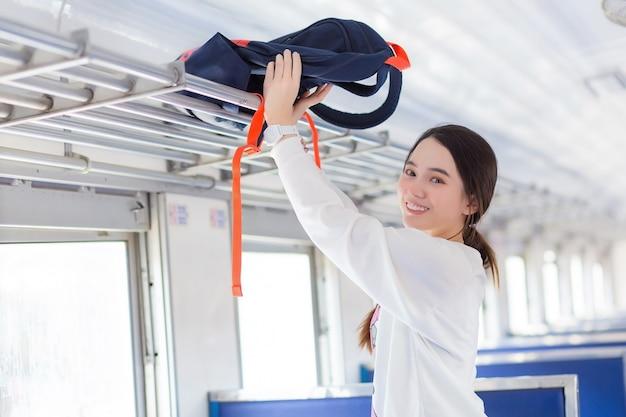 Azjatka w białej koszuli podróżuje pociągiem na szczęśliwe wakacje, niosąc torbę do skrytki sta