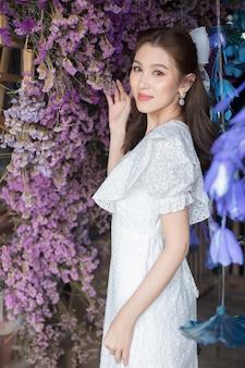 Azjatka w białej sukni stoi w dobrym nastroju wśród turkusowych kwiatów