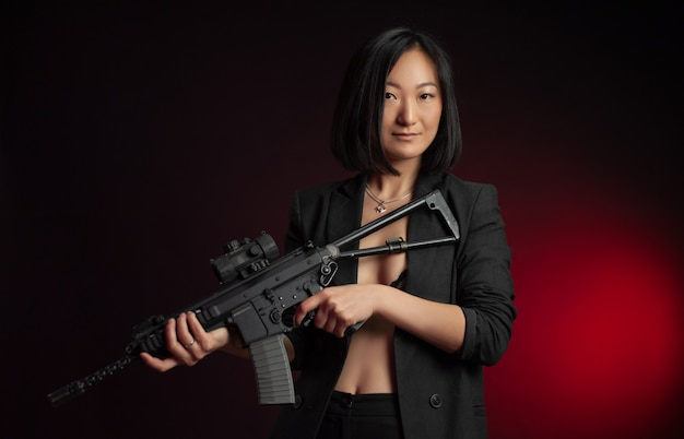 Azjatka w kurtce z karabinem automatycznym w rękach wojowniczka mafii