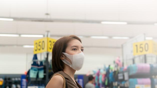 Azjatka w masce na twarzy w domu towarowym, podczas kryzysu związanego z koronawirusem lub epidemii covid19.