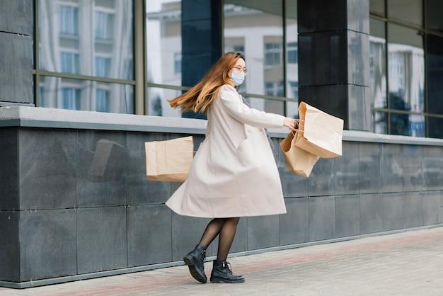 Azjatka w płaszczu, okularach i masce medycznej stoi na ulicy, trzymając w rękach paczkę.