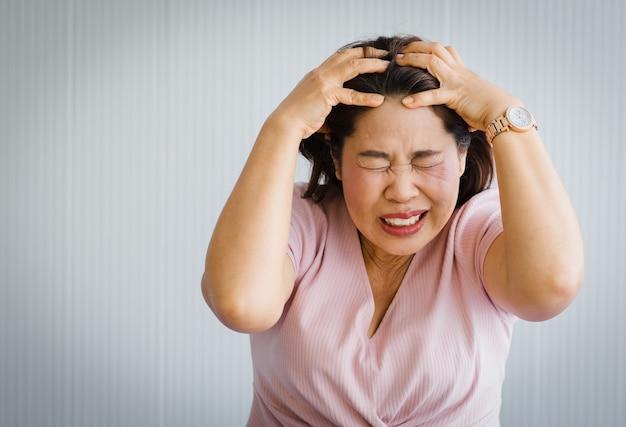 Azjatka w średnim wieku, starsza kobieta, odczuwa ból spowodowany nagłym bólem głowy i atakiem udaru mózgu i trzyma się za głowę z wykrzywioną i wykrzywioną twarzą. pojęcie problemu mózgu i głowy.