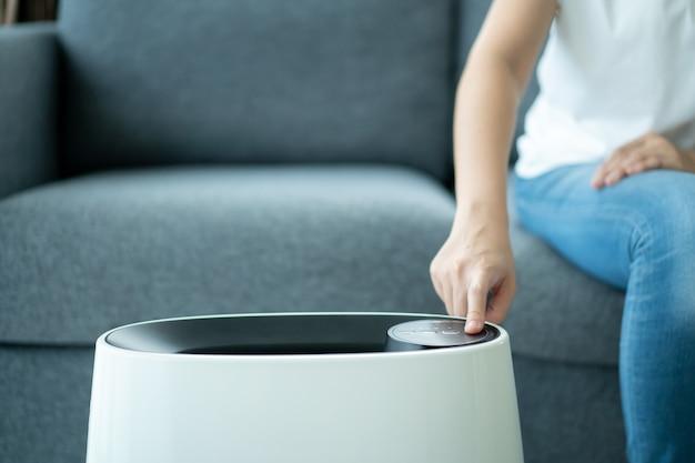 Azjatka włączająca nowoczesny oczyszczacz powietrza przebywając w salonie, oczyszczacz powietrza to popularne urządzenie - domowy prąd. oczyszczacz powietrza może pomóc w oczyszczeniu powietrza.